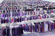 Big clothing store, rows with hangers with pants and t-shirt