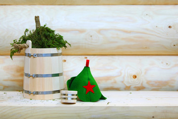 wooden bucket with fir broom and green helmet lie on shelve