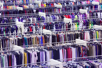 Large clothing store, many rows with hangers with skirts