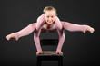 Girl gymnast wearing in pink suit took graceful pose at chair