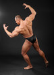 Undressed tanned bodybuilder shows muscles of arms and back