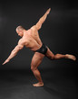 Undressed tanned bodybuilder takes graceful pose in studio