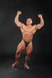Undressed tanned smiling bodybuilder raises his fists up