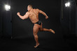 tanned bodybuilder takes graceful pose of running in studio