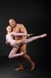 Undressed sunburnt bodybuilder holds graceful girl in studio