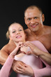 sunburnt bodybuilder hugs with girl and represents heart