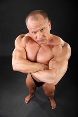 Undressed tanned bodybuilder looks menacing inside black studio