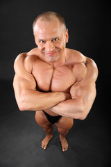 Undressed barefoot tanned bodybuilder smiles inside black studio