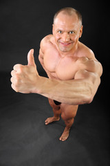 Undressed tanned bodybuilder smiles and thumbs up