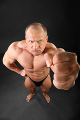Undressed formidable tanned bodybuilder punches to camera