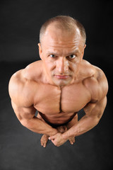 Undressed formidable tanned bodybuilder looks at camera