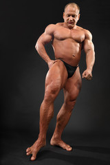 Undressed tanned bodybuilder touches floor by toe