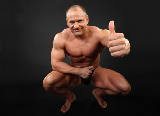 Undressed tanned smiling bodybuilder sits and thumbs up