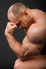 Undressed tanned bodybuilder leaned his forehead on fist