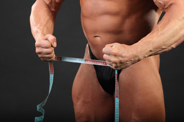 Undressed tanned bodybuilder holds measuring tape in studio