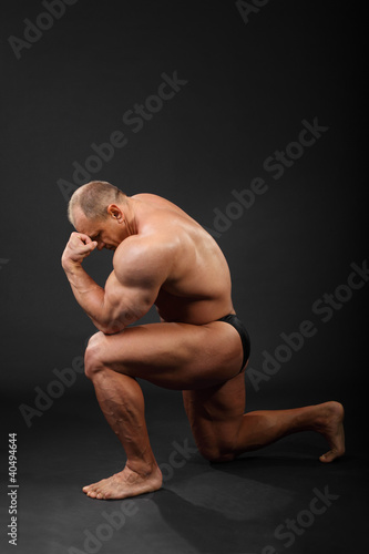 Undressed tanned bodybuilder stands on one knee and thinks