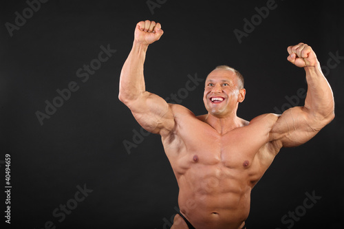 Undressed tanned happy bodybuilder raises his fists up
