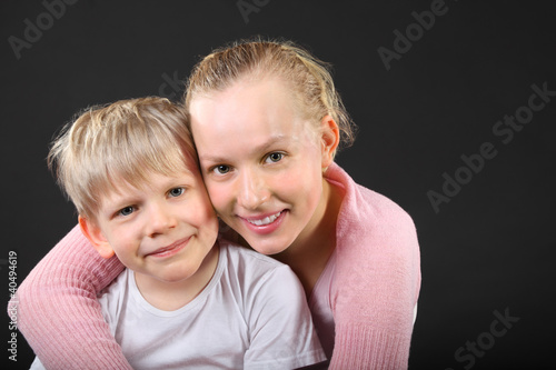 Little blond brother and beautiful sister embrace on black