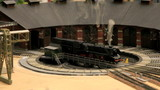 fuming steam locomotive entering in the depot round