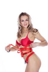 Sportliche Frau in roten Dessous mit Schleifchen zu Weihnachten