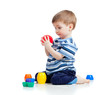 Funny little child is playing with cup toys while sitting on flo