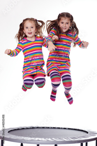Two young girls jumping on a trampoline
