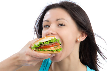 Young woman eating tasty fast food unhealthy burger