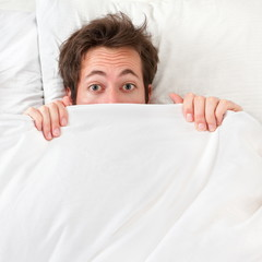 Scared man hiding in bed