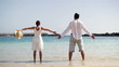 Couple with wide open arms standing on the beach