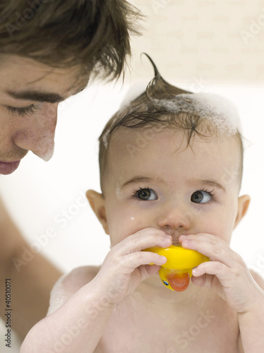 Baby girl playing with toy while her father bathing for her