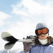 Woman in ski goggles holding skis
