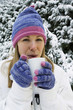 Woman drinking hot beverage, standing outdoor