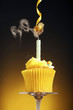 A cupcake with blown out candle and a frog hanging from a streamer