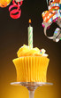 Close-up of a cupcake with a candle and streamers