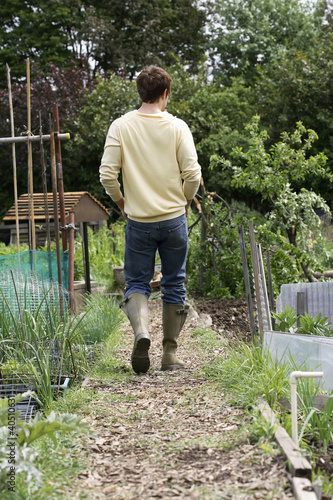 Man in gardening boots walking in community garden