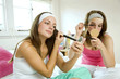 Girls applying make-up in the bedroom