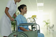 Nurse pushing woman on wheelchair, woman holding a vase of flowers