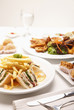 Club sandwich, fried yam puffs, fried puff pastries, and bruschetta served with chicken wings