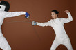 Woman with fencing foil attacking her opponent