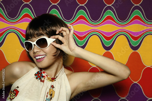 Woman smiling while adjusting her sunglasses