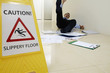 Businessman slipping beside Caution sign