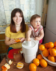mother and daughter making  orange juice