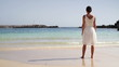 Woman in white dress standing on beautiful tropical beach