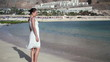 Woman in white dress standing on the beach