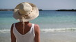Woman in summer hat standing on beautiful tropical beach
