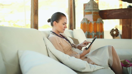 Happy young woman with tablet computer sitting on sofa