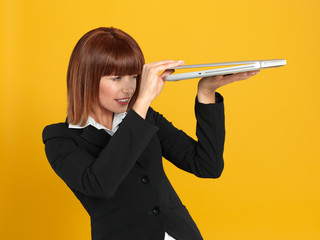 attractive, young businesswoman peeping into laptop