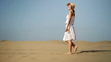Young woman walking on the desert, slow motion