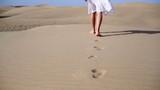 Woman feet walking on the desert