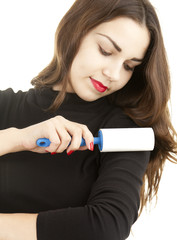 young woman cleaning dust with lint roller